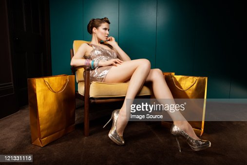 Young woman sitting on chair with shopping bags