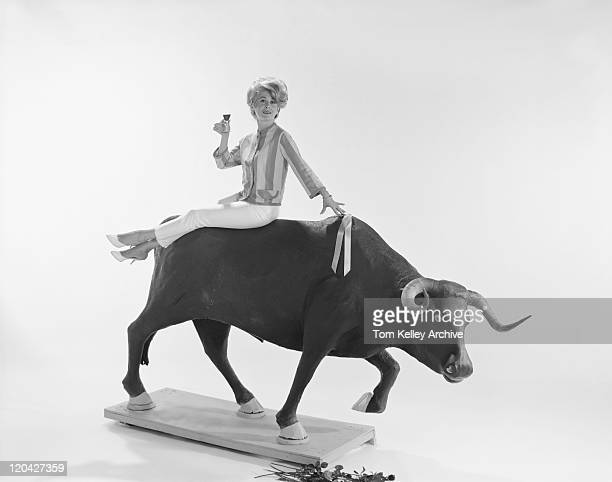 Young woman sitting on charging bull, smiling, portrait