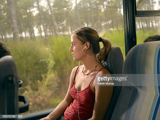 Young woman sitting on coach wearing earphones