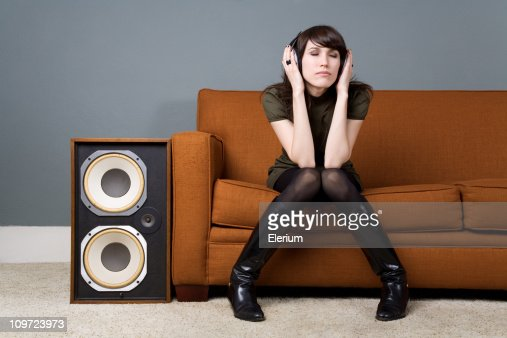Young Woman Sitting on Couch and Listening to Music : Stock Photo