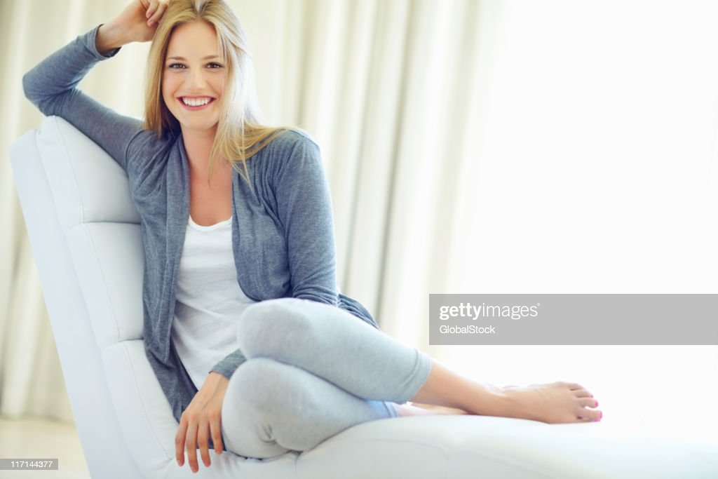 Young woman sitting on couch : Stock Photo