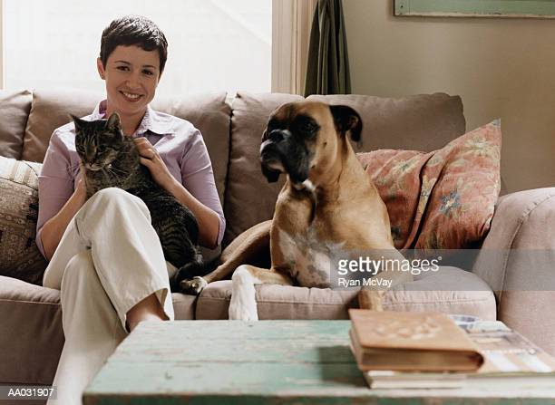Young Woman Sitting on Couch with Dog and Cat