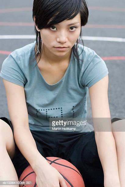 Young woman sitting on court with basketball