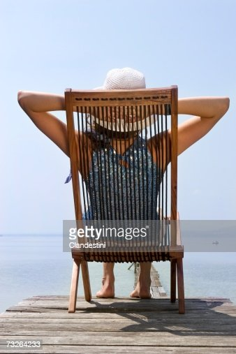 Young woman sitting on deckchair on jetty, hand behind head, rear view