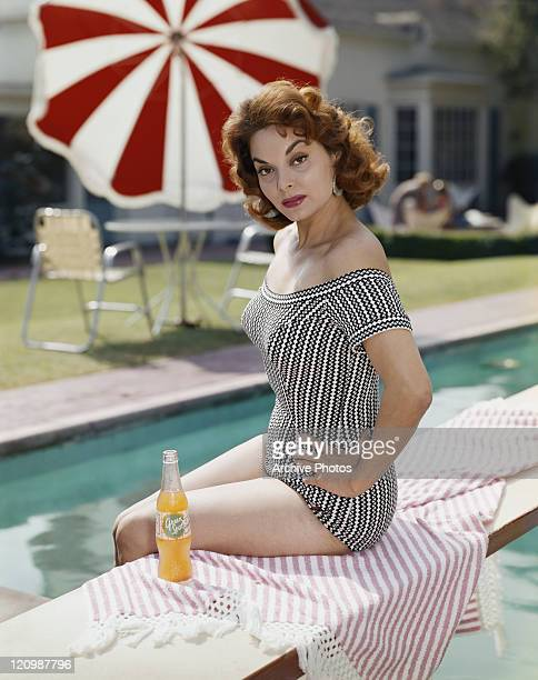 Young woman sitting on diving board with drink, portrait