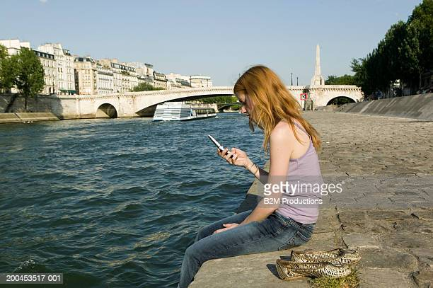 Young woman sitting on edge of quay, looking at mobile phone