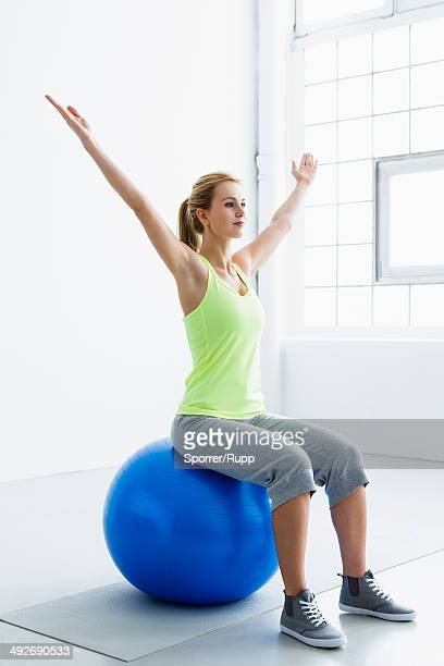 Young woman sitting on exercise ball, arms raised