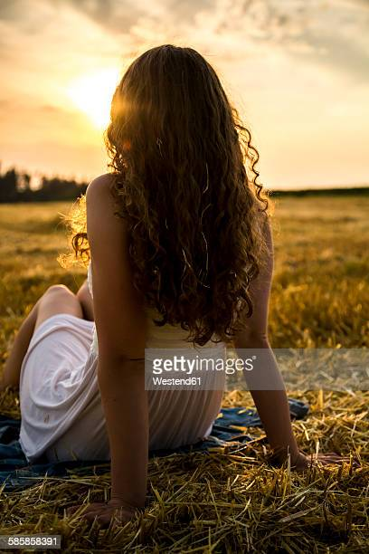 Young woman sitting on field in the evening