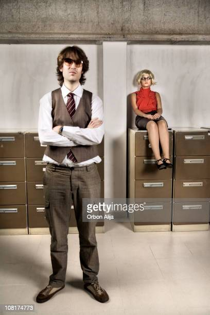 Junge Frau sitzt am Aktenschrank und Geschäftsmann stehend