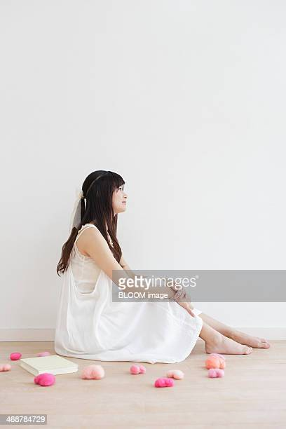 Young woman sitting on floor and daydreaming