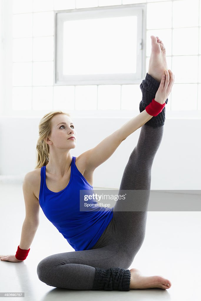 Young woman sitting on floor in gymnasium