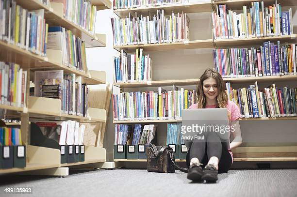 Young woman sitting on floor in library using laptop