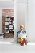 Young woman sitting on floor in office using laptop