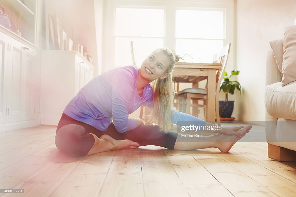 Young woman sitting on floor wearing sports clothing, stretching
