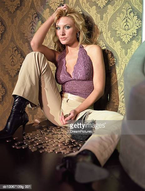 Young woman sitting on floor with coins, portrait