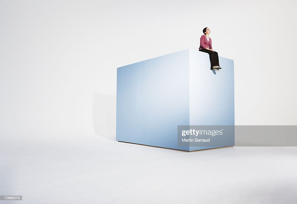 Young woman sitting on giant box