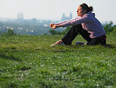Young woman sitting on grass in sport clothes, cityscape in background