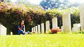 Young Woman Sitting On Grassy Field At Kirkee War Cemetery