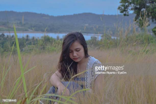 Young Woman Sitting On Grassy Field