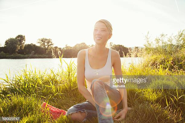 Young woman sitting on grassy riverbank, Danube Island, Vienna, Austria