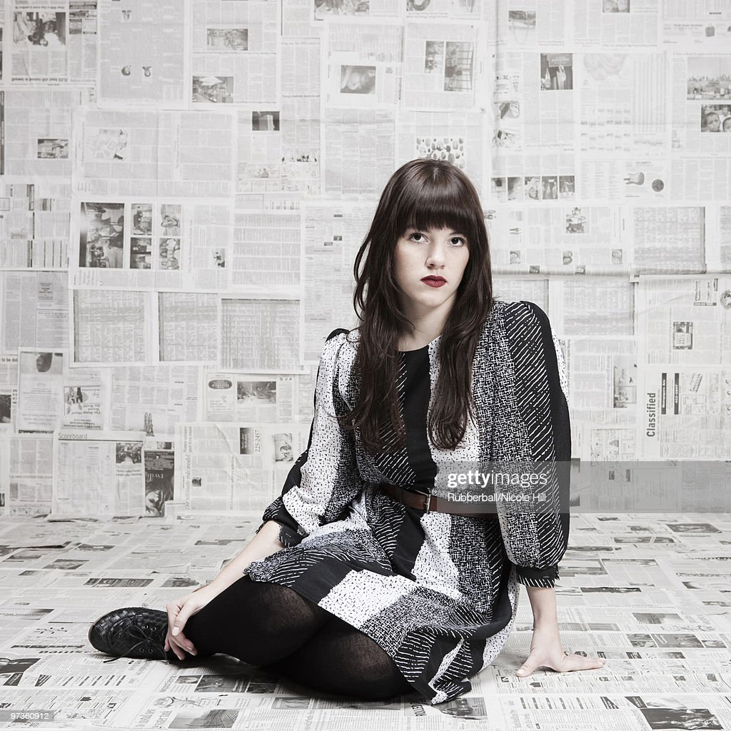 Young woman sitting on ground in room covered with newspapers, portrait, studio shot : Stock Photo
