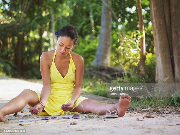 Young woman sitting on ground playing cards