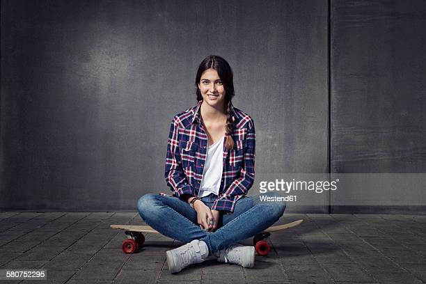 Young woman sitting on her longboard