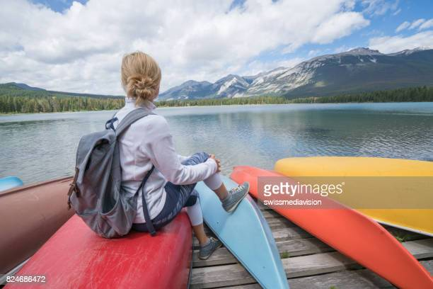 Young woman sitting on kayak by the lake