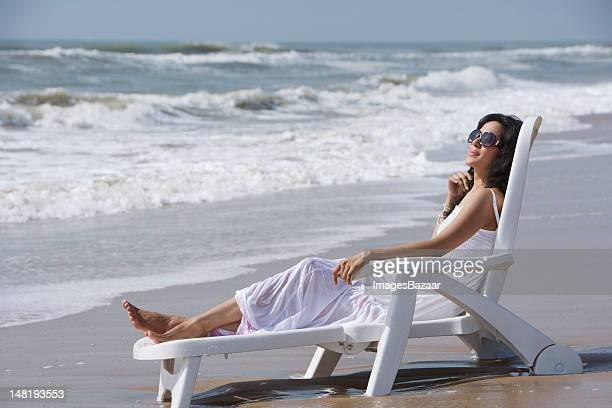 Jeune femme assise sur une chaise longue sur la plage