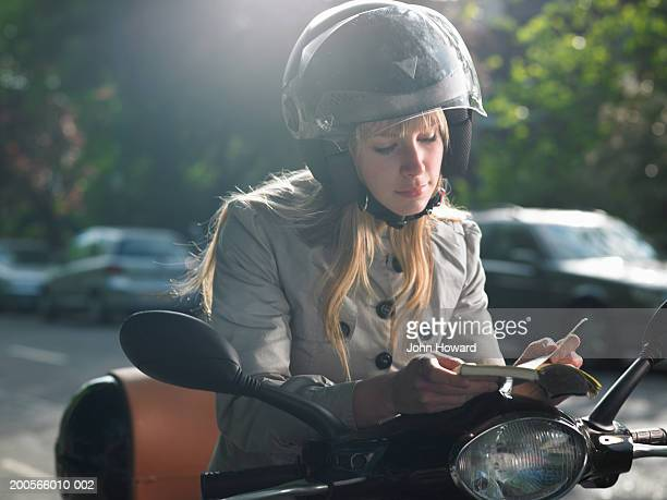 Young woman sitting on moped, reading book