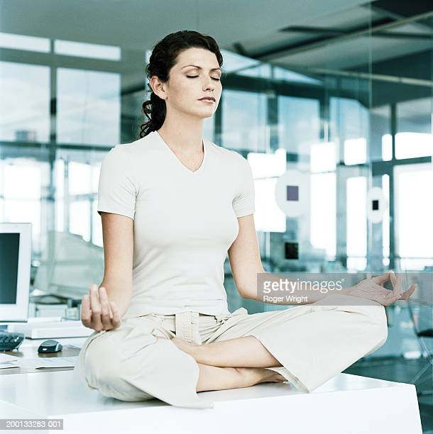 Young woman sitting on office table, cross legged, eyes closed
