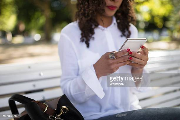 Young woman sitting on park bench using her smartphone, close-up