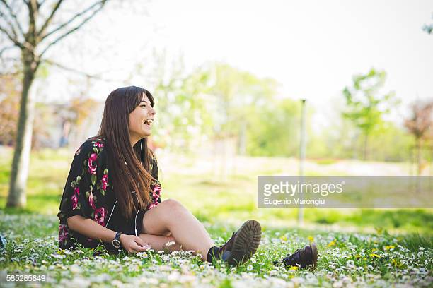 Young woman sitting on park grass listening to earphones