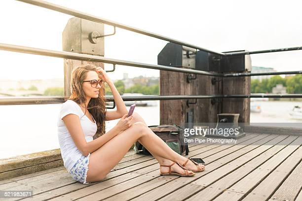 Young woman sitting on pier using cell phone