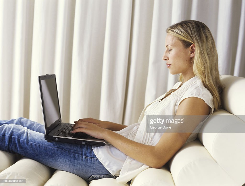 photo young woman sitting on reclining chair using laptop side view