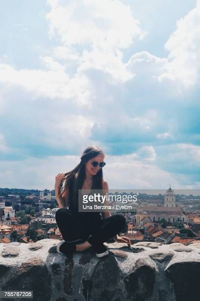 Young Woman Sitting On Retaining Wall Against Cityscape