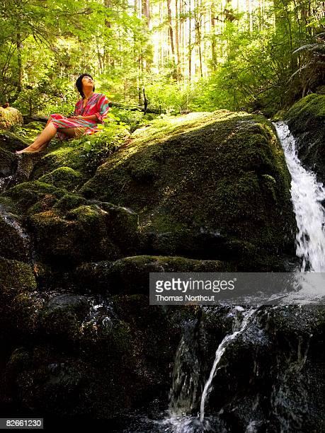 Giovane donna seduta su roccia vicino al ruscello