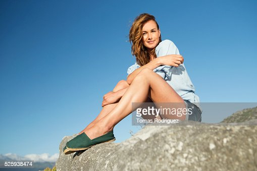 Young woman sitting on rock : Stockfoto