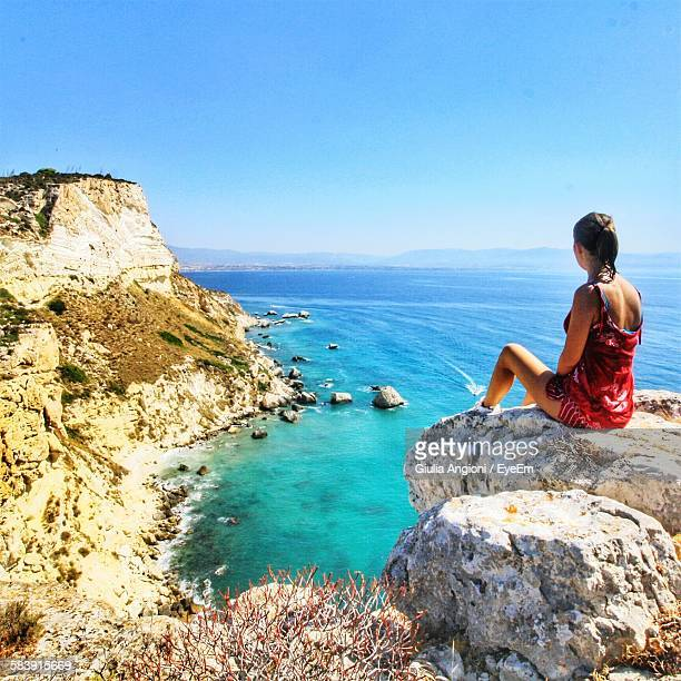 Young Woman Sitting On Rocks At Seaside Against Clear Sky