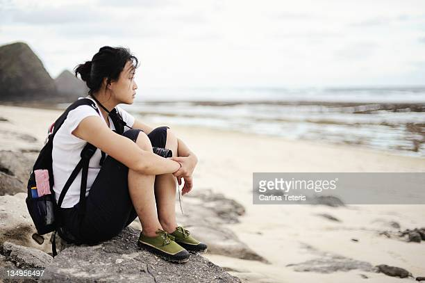 Young woman sitting on rocks on sea