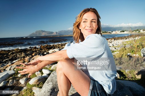 Young woman sitting on rocky beach : Stock-Foto