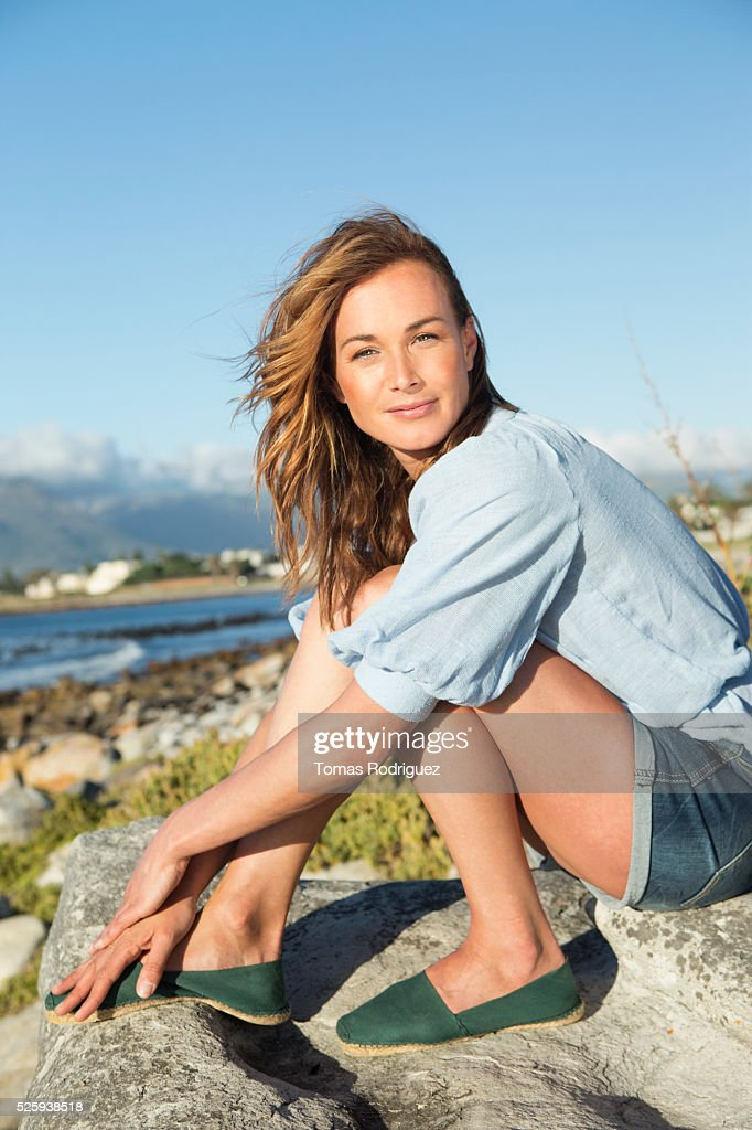 Young woman sitting on rocky beach : Stockfoto
