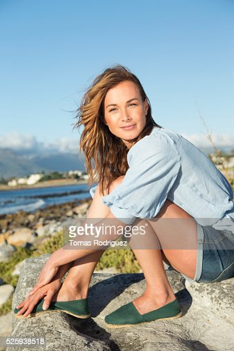 Young woman sitting on rocky beach : Foto de stock