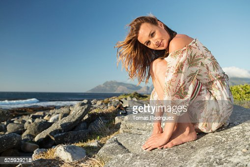 Young woman sitting on rocky beach : Photo