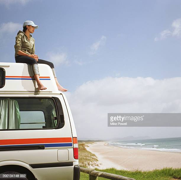 Young woman sitting on roof of camper van parked on beach