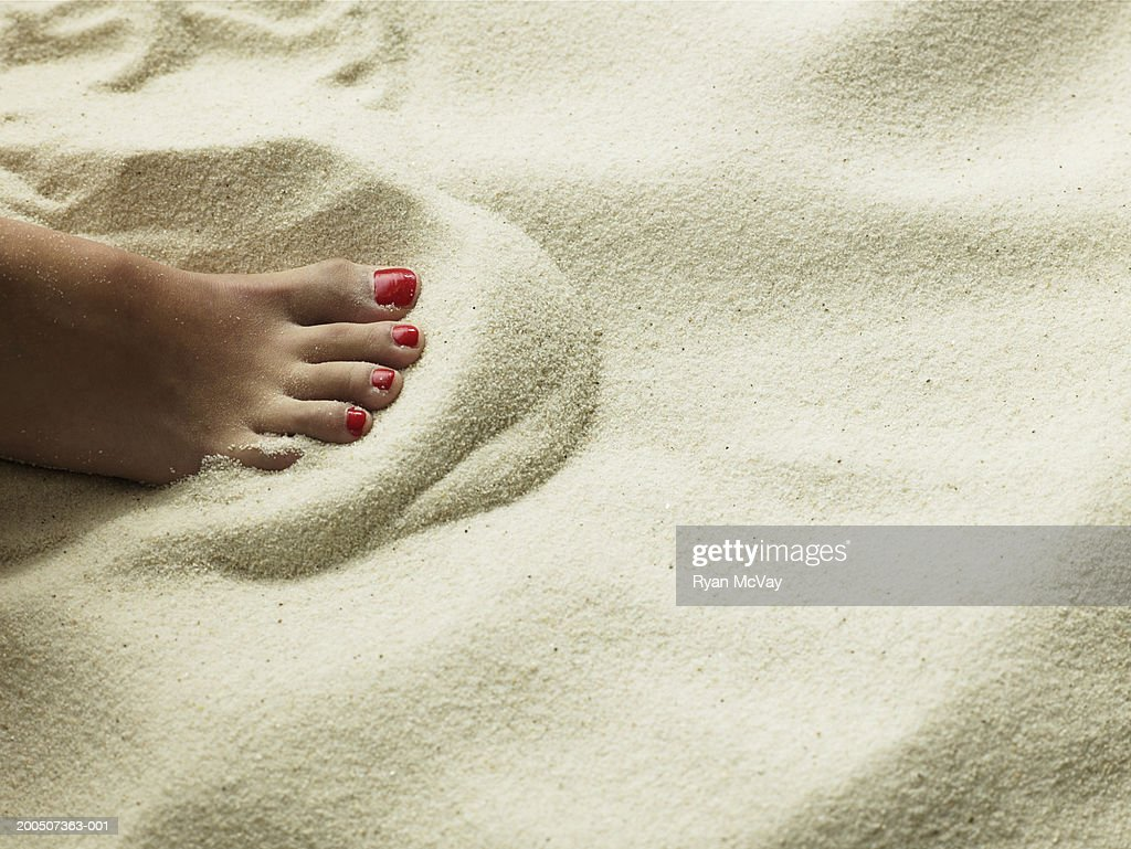 Young woman sitting on sand, close-up of foot : Stock Photo