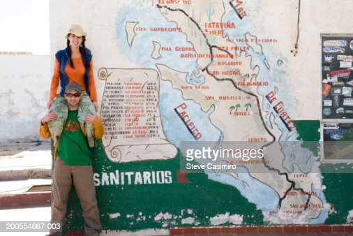 Young woman sitting on shoulders of young man standing by outdoor map of Baja California : Stock Photo
