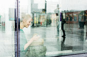 Young woman sitting on sill seen through glass at railroad station