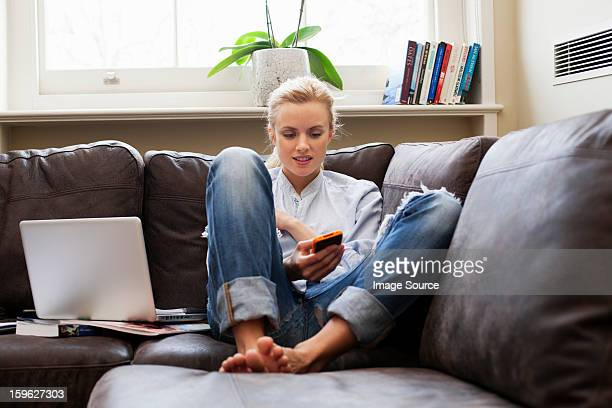 Young woman sitting on sofa and looking at smartphone
