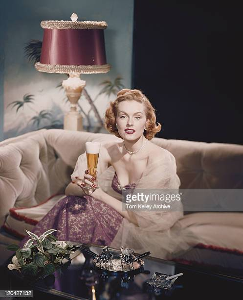 Young woman sitting on sofa holding beer glass, smiling, portrait